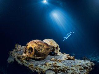 Una turista con esnórquel flota en un cenote llamado Las Calaveras, cerca de Tulum. Los mayas de la zona obtenían el agua para beber de este cenote hasta hace unos 30 años, cuando unos buzos encontraron huesos. Los arqueólogos han identificado los restos de más de un centenar de personas, normalmente bajo las oscuras aguas. paulnicklen.com